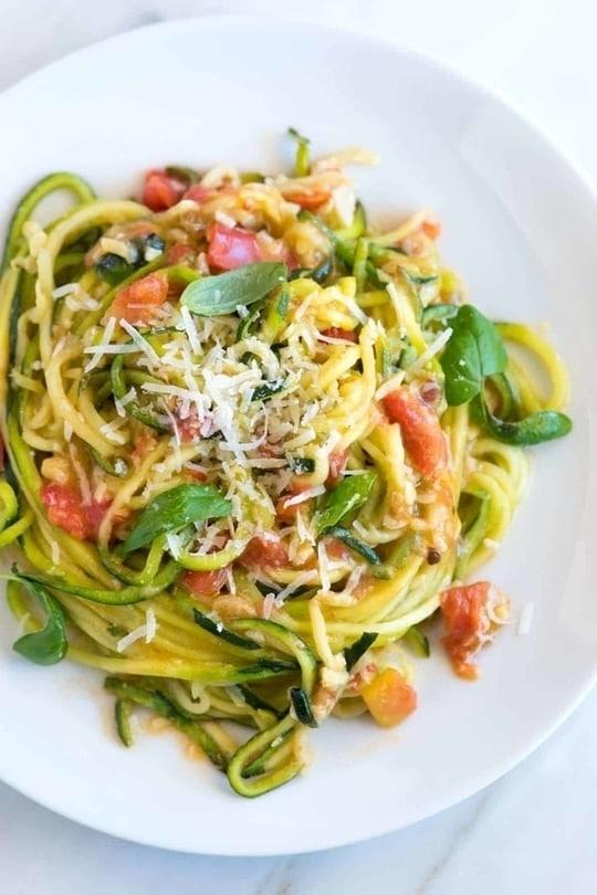 Cuketové špagety se sýrem, zeleninou a bazalkou, na bílém kulatém talíři