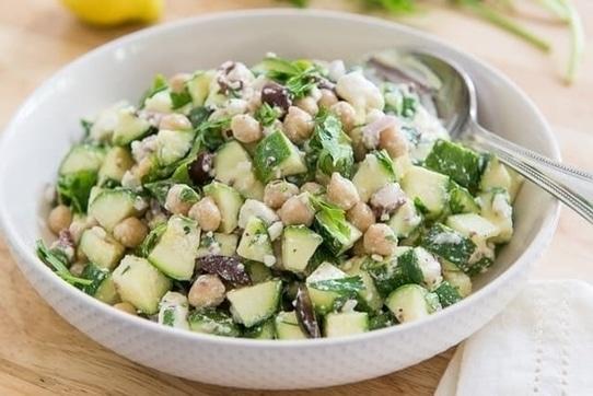 Cuketový salát s cizrnou, cibulí, olivami a feta sýrem, v bílém hlubokém talíři