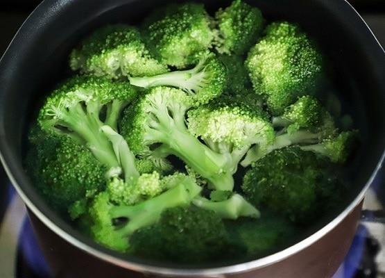 Zelená uvařená brokolice, natrhaná na růžičky v nerezovém hrnci.