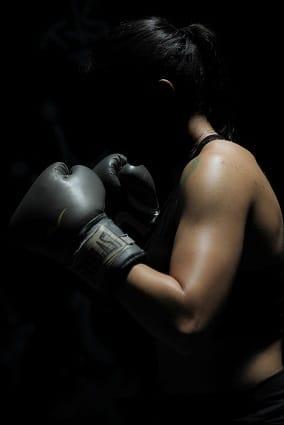 Boxující žena zvládá stres pomocí cvičení ne přejídání a přitom spaluje tuky.
