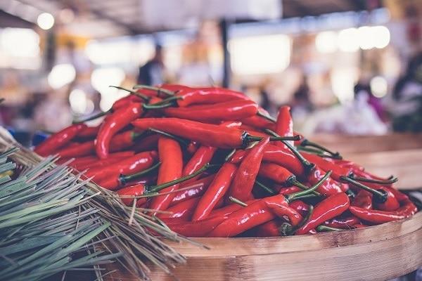 Hromada čerstvým chilli papriček na dřevěném podnose.