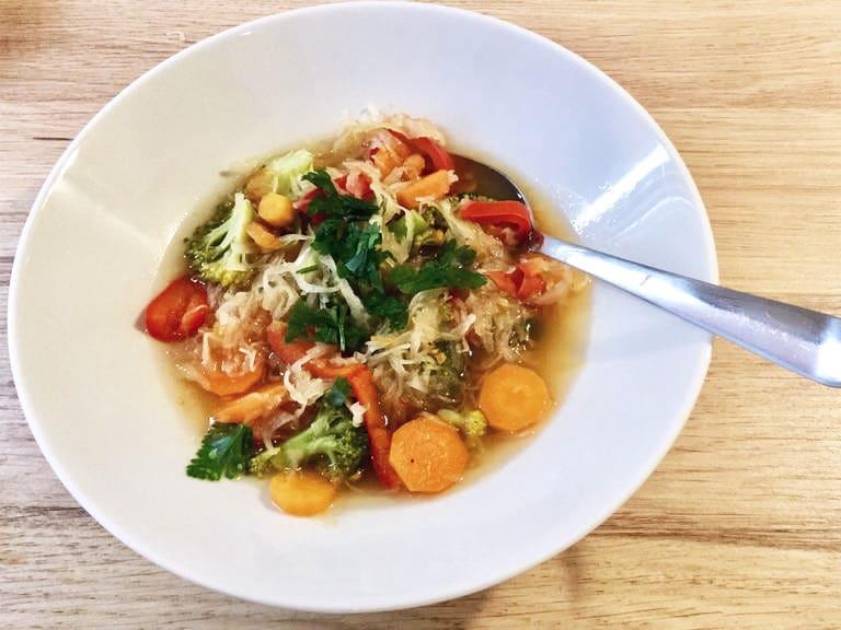 Bílý talíř, plný kysaného zelí a zeleniny.