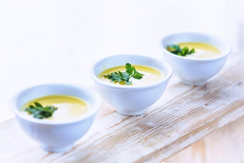 Tři bílé misky s pórkovou polévkou, ozdobené zelenou bylinkou.
