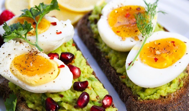 Vařená vejce na pečivu se zelenou pomazánkou.