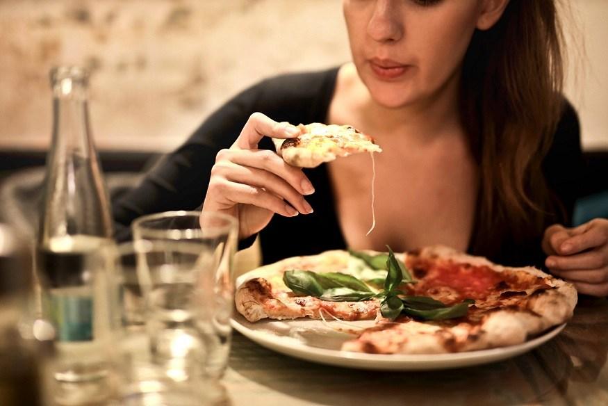 Žena s plným talířem pizzy, který má před sebou.