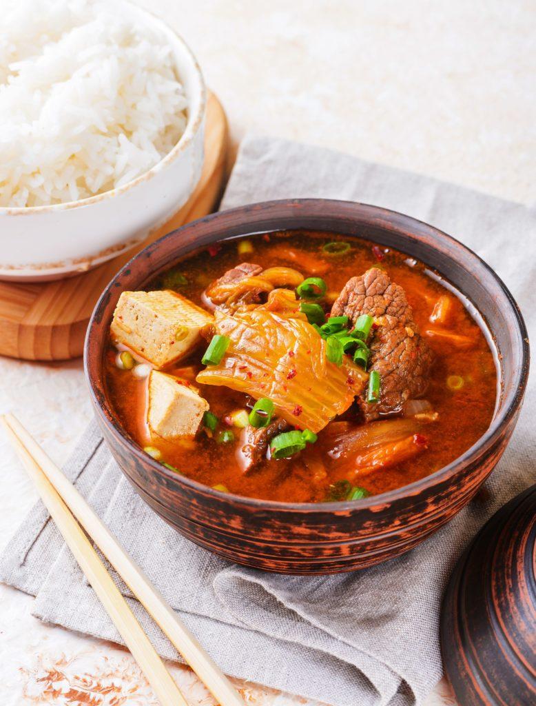 kimchi stew s rýží v miskách s jídelními hůlkami