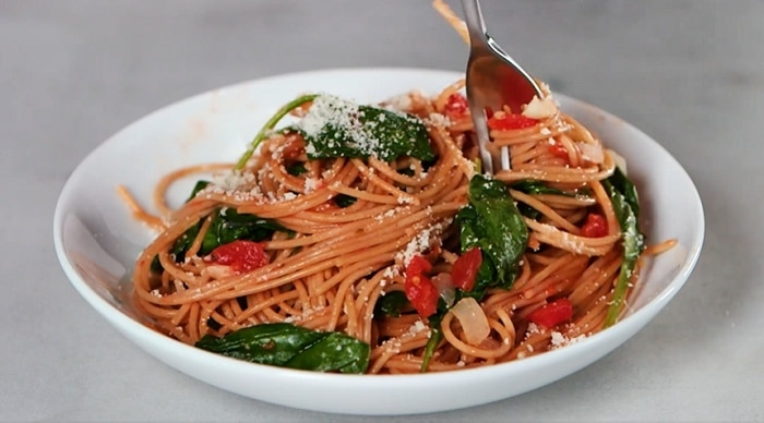 Špagety s listovým špenátem v bílém talíři.