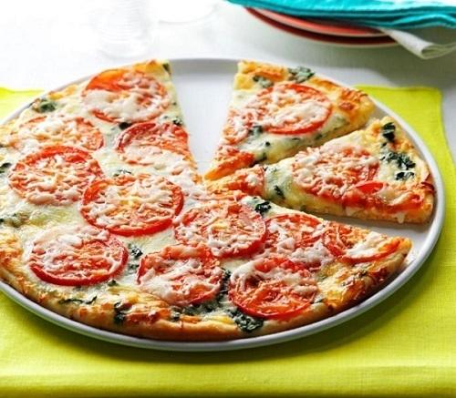 Špenátová pizza s mozzarellou a rajčaty na bílém talíři.
