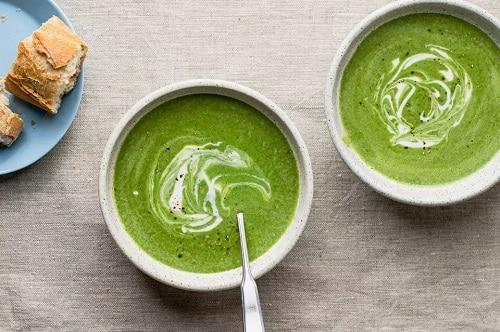 Špenátová polévka se smetanou v bílém talíři.