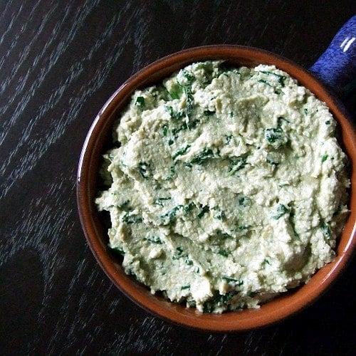 Špenátová pomazánka ze sýru Cottage, tvarohu a jogurtu v hnědé misce.