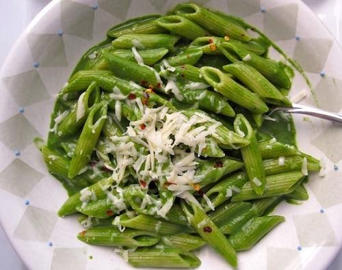 Těstoviny se zelenou špenátovou omáčkou, sypané parmazánem.