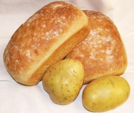 Dva bochníky bramborového chleba se dvěma brambory.