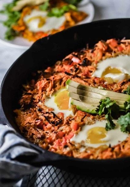 Zdravá pečená snídaně s brambory, vejci a avokádem.