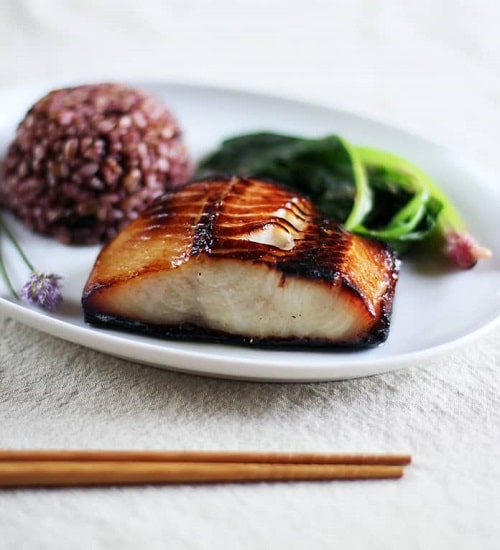 Filet z tmavé tresky, podávaný se salátem a kopečkem divoké rýže.