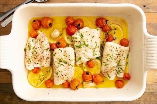 Zapečená treska se zeleninou, citronem, česnekem a olivovým olejem, zdobená čerstvými bylinkami.