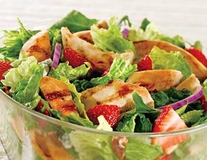 Skleněná mísa báječného Caesar salátu s kuřecím a jahodami