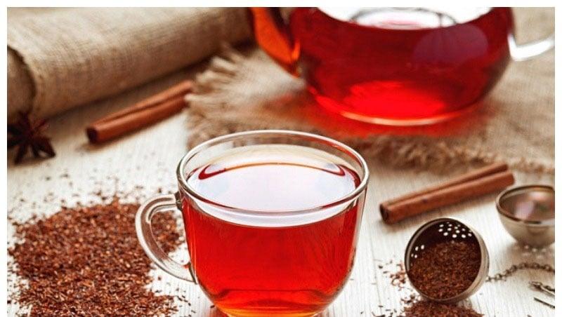 Pu-erh červený čaj ve skleněném hrnku se skořicí.