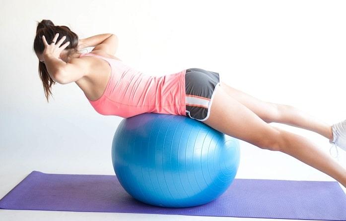Žena leží na míči. Komplexní cvik na posílení zádových svalů.