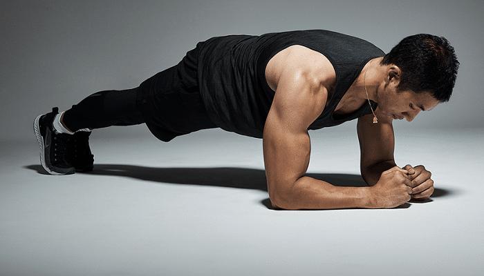 Svalnatý muž posiluje břišní svaly. Cvik plank.
