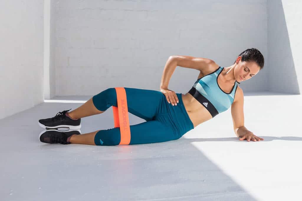Žena cvičí boční stranu stehen