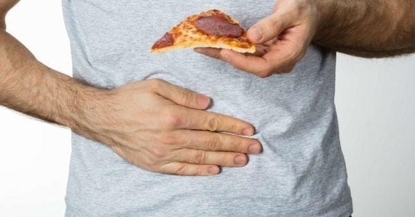 Člověk trpící celiakií a pizza obsahující lepek