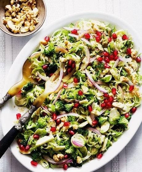 Salát z brokolice a růžičkové kapusty s cibulí, ořechy a granátovým jablkem, v bílé oválné míse