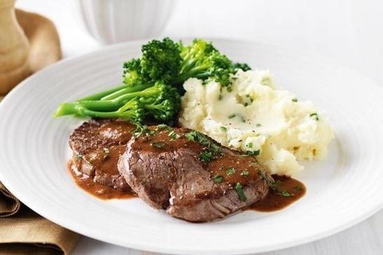 Steak z hovězí svíčkové s brokolicí a bramborovou kaší, na bílém kulatém talíři