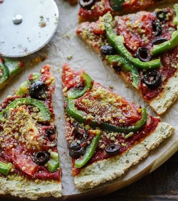Cuketová pizza s rajčatovou omáčkou, paprikou a olivami, na dřevěném tácu