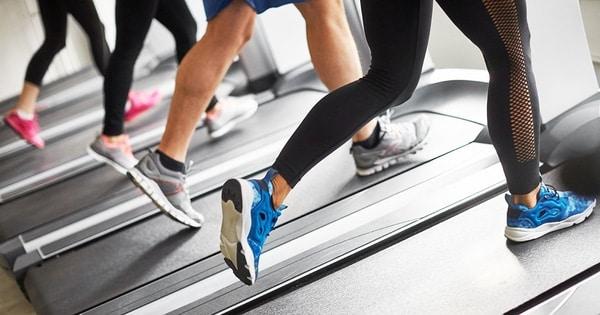 Lidé trénující na běžících pásech