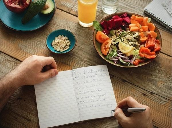 Zdravé potraviny a člověk zapisující si jídlo do jídelníčku