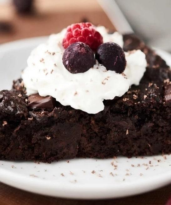 Kakaový cuketový koláč s ovocem na bílém kulatém talíři