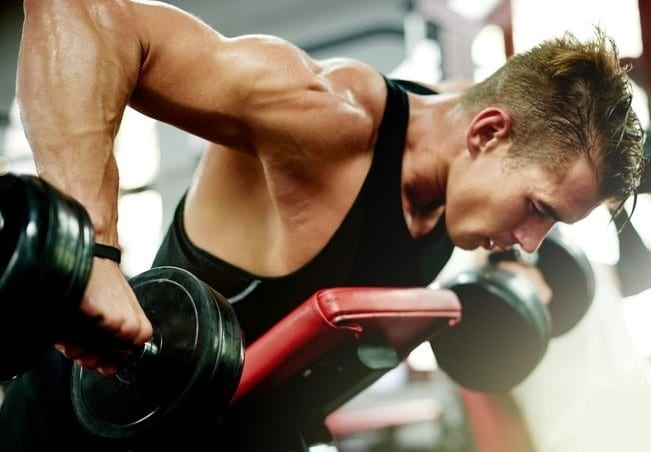 Fotka mladého muže cvičícího v posilovně