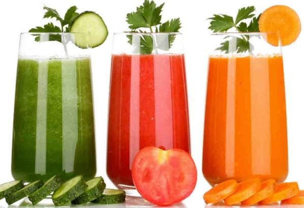 Okurkový, rajčatový a mrkvový džus ve vysokých skleničkách, s bylinkovou ozdobou