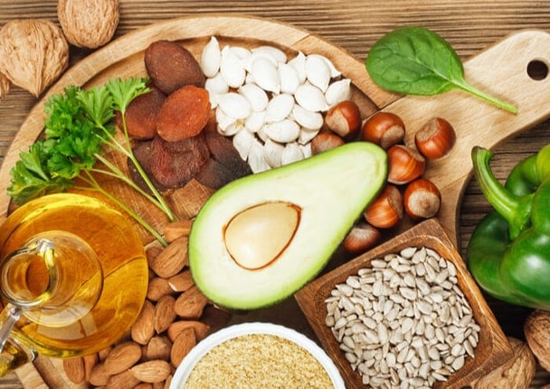 Výběr ovoce, ořechů, bylinek, zeleniny a oleje na dřevěném prkýnku