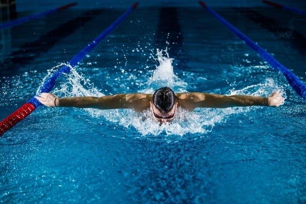 Člověk trénující výdrž při plavání v bazénu