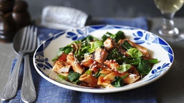 Celozrnné těstoviny s rajčatovou omáčkou, zeleninou a bylinkami na modrobílém talíři