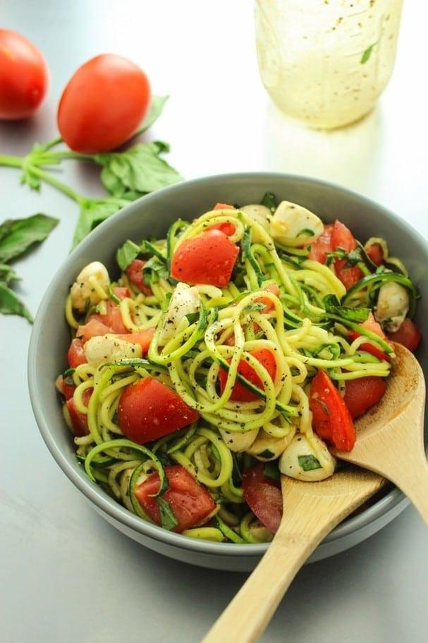 Cuketové špagety s caprese směsí v šedé keramické misce s vařečkami