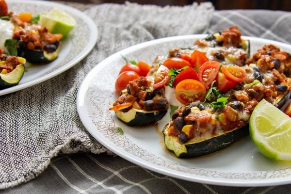Dietní cukety plněné burrito směsí s rajčátky a limetkou na bílých talířích
