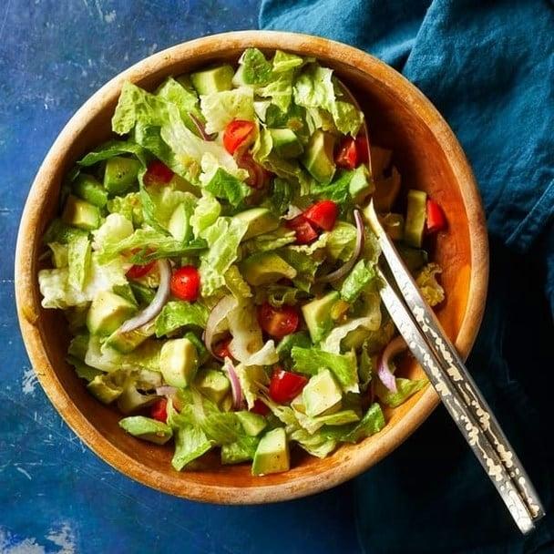 Zeleninový salát na guacamole styl v hnědé keramické misce s příborem