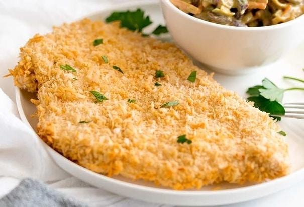 Kuřecí řízek pečený v troubě s bylinkami na bílém kulatém talíři