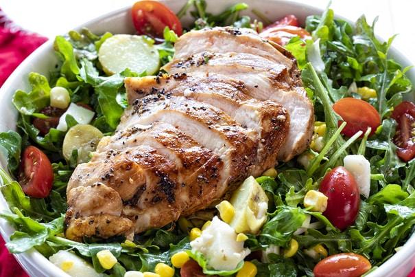 Opečené kuřecí prso se zeleninovým salátém v bílé keramické míse