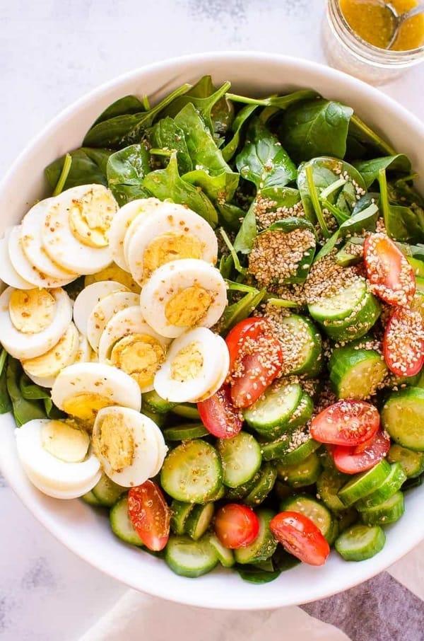 Špenátový salát s vajíčky, sezamovými semínky, okurkou a cherry rajčátky v bílé míse