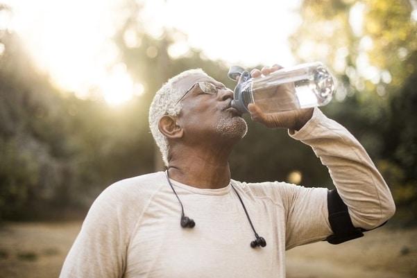 Starší sportovec, který pije čistou vodu - příklad správné hydratace organismu