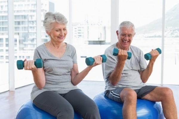Starší lidé při cvičení s činkami na gymnastických míčích