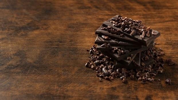 Tabulky hořké čokolády s čokoládovými hoblinkami na dřevěném stole