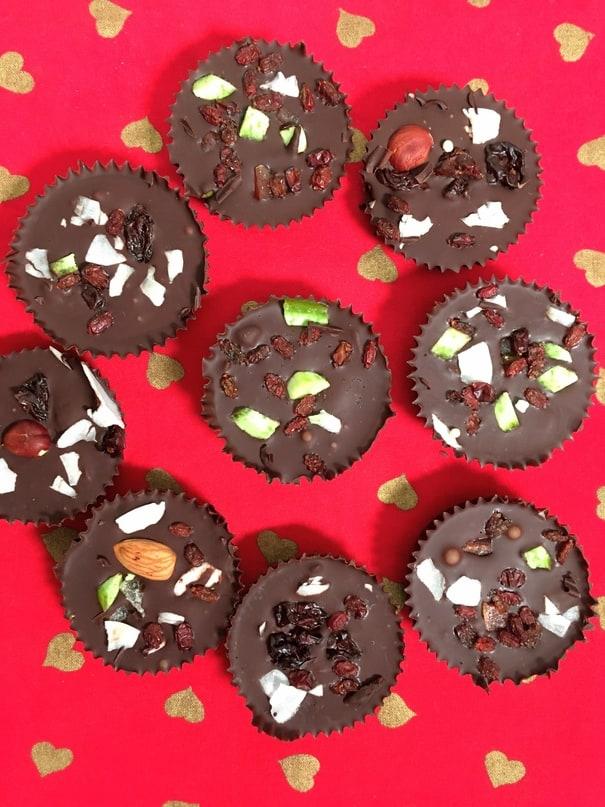 Vánoční čokoládové košíčky s oříšky a rozinkami na růžovém prostírání