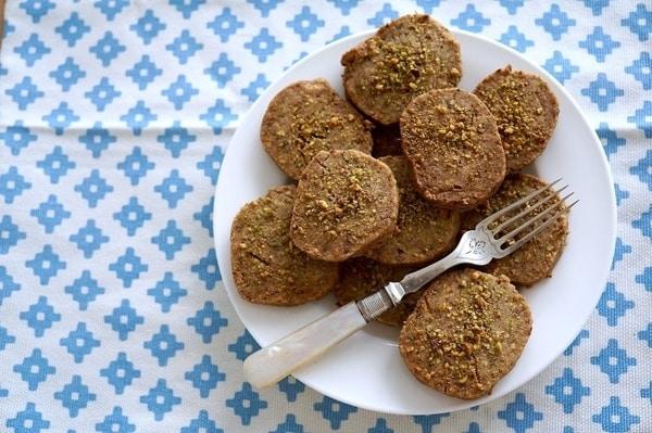 Pistáciovo-mrkvové vánoční sušenky na bílém keramickém talířku s vidličkou
