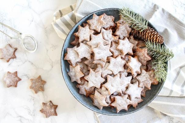 Zdravé vánoční mandlové hvězdičky se skořicí a cukrem v modré keramické misce